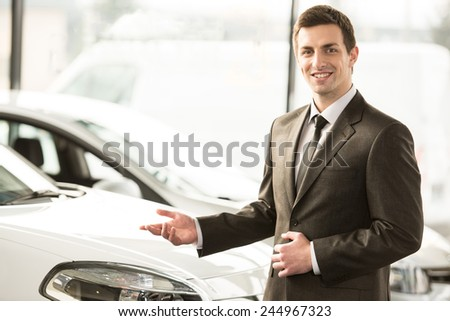 Young man consultant in showroom is standing near car. Top view. - stock photo
