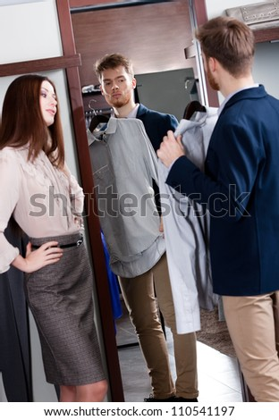 Young man consults with girlfriend while selecting a spruce shirt - stock photo