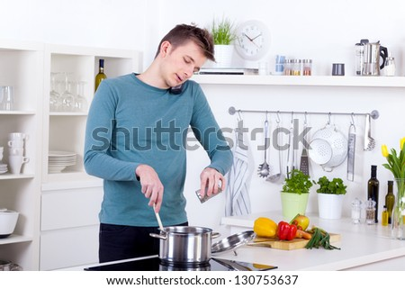young man cooking a meal and talking on the phone in his kitchen - stock photo