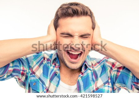 Young man covering his ears and shouting - stock photo