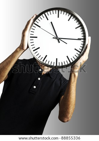 young man covering his face with a clock over grey background - stock photo