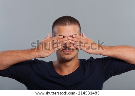 Young man covers eyes with his hands. Studio Shot. - stock photo