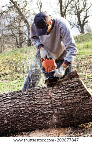 Young man cutting trees using an electrical chainsaw in the countryside - stock photo