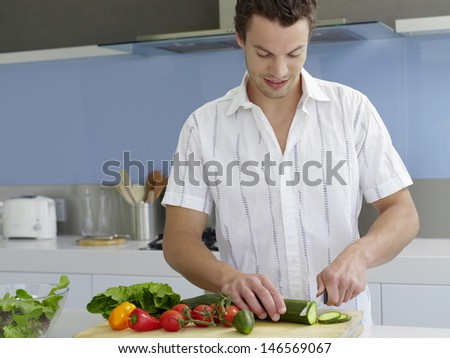 Young man cutting vegetables on wooden board in domestic kitchen - stock photo