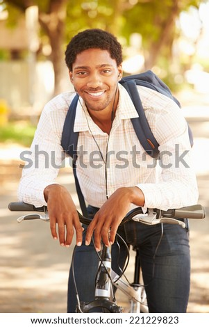 Young Man Cycling Along Street To Work - stock photo