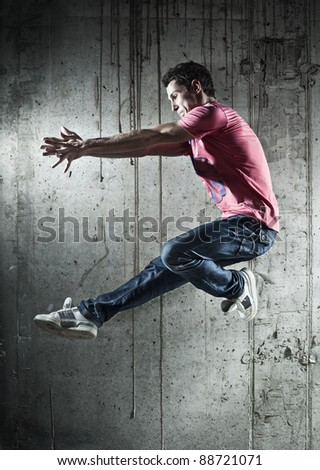 Young man dancer jumping. On wall background. - stock photo