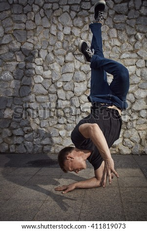 Young man dancing and balancing head down on the land in the city - stock photo