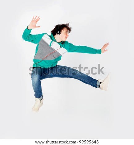 Young man dancing and jumping in studio - stock photo