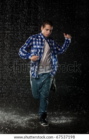 Young man dancing in water under rain on a black background.  Modern dances. - stock photo