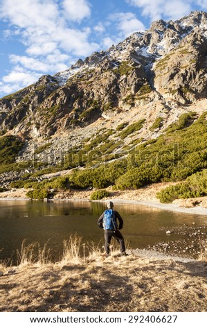 Young Man Delighting the Mountains over the Pond  - stock photo