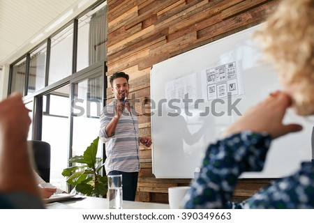 Young man discussing new mobile application design on white board with colleagues during a meeting. Business presentation in boardroom. - stock photo