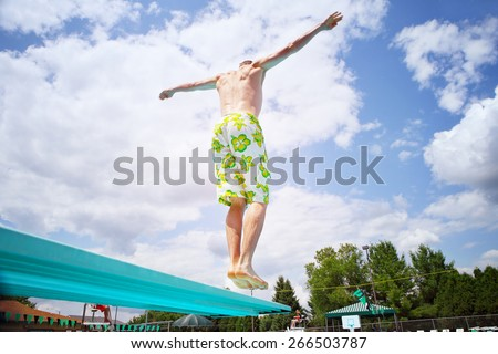 Young man diving off a diving board - stock photo