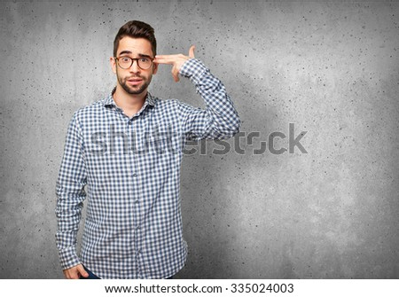 young man doing a suicide gesture - stock photo
