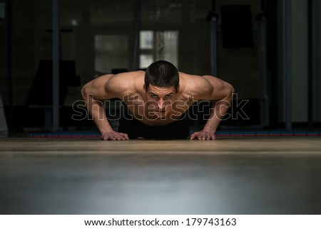 Young Man Doing Press Ups In Gym - stock photo