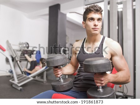 Young man doing shoulders exercises, resting.Woman in background. - stock photo