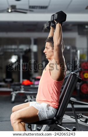 Young man doing shoulders workout in the gym, with dumbbells - stock photo