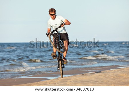 Young man doing wheelie with bicycle in beach - stock photo