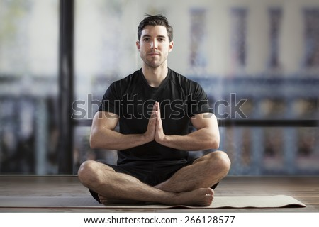 young man doing yoga in office - stock photo