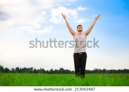 Young man doing yoga in park. Healthy lifestyle. - stock photo
