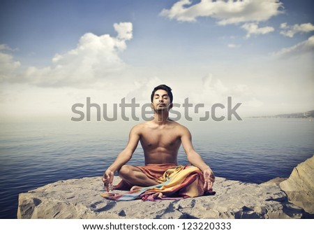 Young man doing yoga on a cliff - stock photo