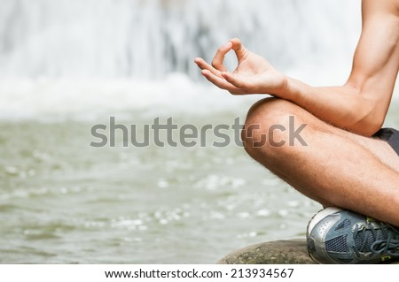 Young man doing yoga with waterfall in the background healthy lifestyle. Zen meditation and Spa concept with space for adding text - stock photo