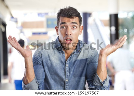 young man doubt gesture in a shopping center - stock photo