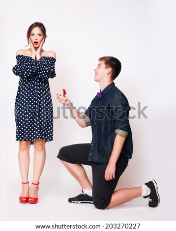 young man down on his knee proposing to girlfriend - stock photo