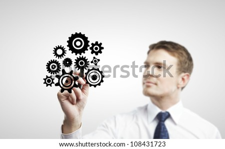 young man drawing abstract cog wheel - stock photo