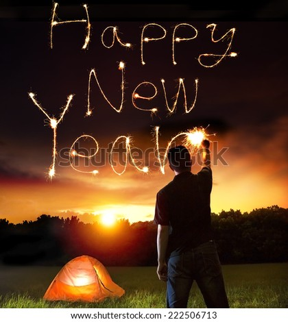 young man drawing happy new year words by sparkling stick. camping on the mountain - stock photo
