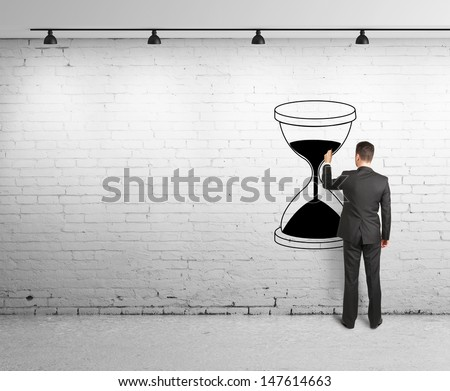 young man drawing hourglass on brick wal - stock photo