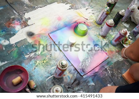 Young man draws a picture with spray paints. - stock photo