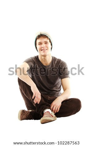 Young man dressed in hip style sitting cross legged against white background - stock photo