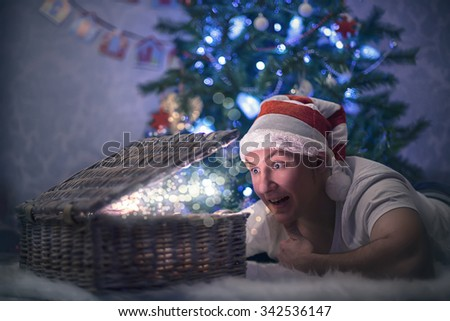 young man dressed in santa hat opening the box that lights from inside - stock photo
