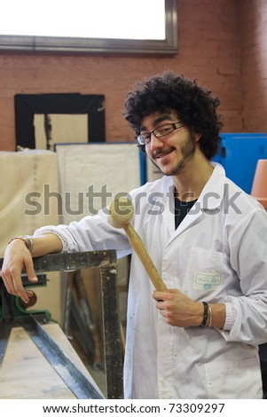 Young man dressed in white with a hammer in his hand - stock photo