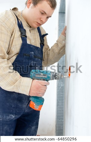 Young man drill a wall for installing power socket - stock photo