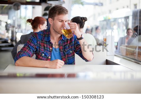 Young man drinking beer in a cafe - stock photo