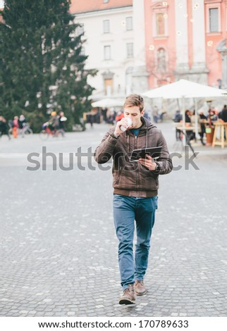 Young man drinking coffee on the go and using tablet computer - stock photo