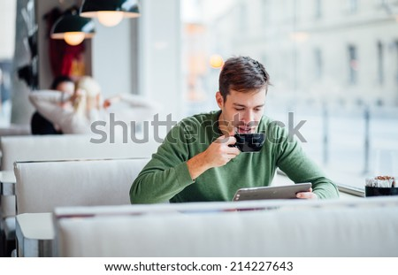 Young man drinking coffee on the street while using tablet computer - stock photo