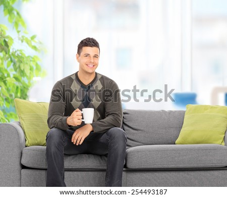 Young man drinking coffee seated on couch at home shot with tilt and shift lens - stock photo
