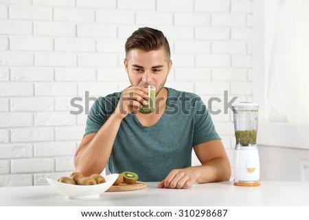 Young man drinking fresh kiwi juice - stock photo