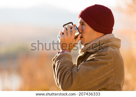 young man drinking hot coffee outdoors in cold winter day - stock photo