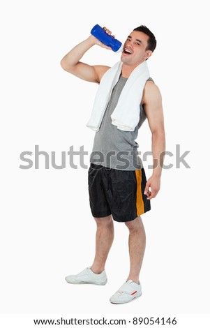 Young man drinking water after workout against a white background - stock photo