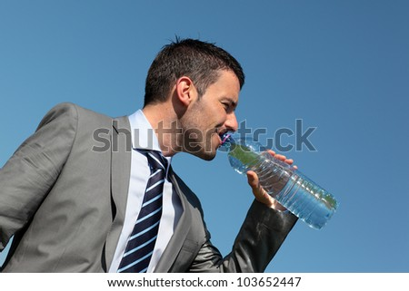 young man drinking water in blue sky - stock photo