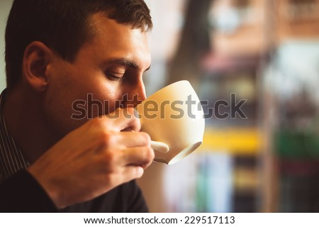 Young man drinks coffee on the street. Man drinks coffee. Young man drinks coffee outdoor. Businessman drinks coffee outdoor. Man drink coffee in cafe. Cozy atmosphere. Student drinks coffee. Coffee - stock photo