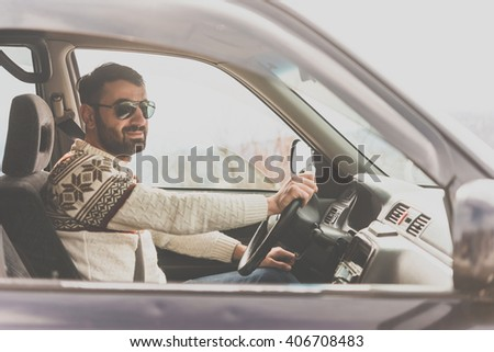 Young man drives a car in mountains. Travel and adventure concept. Toned picture - stock photo