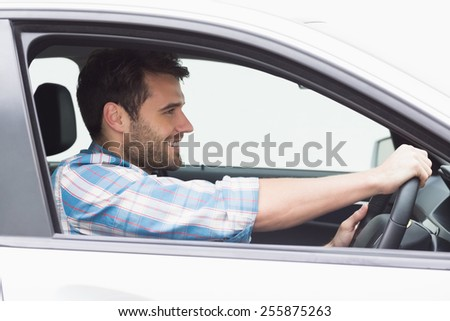 Young man driving and smiling in his car - stock photo