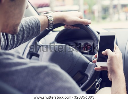 Young man driving car and using mobile phone - stock photo