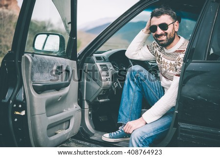 Young man driving the car in the mountains is relaxing at a roadside - stock photo