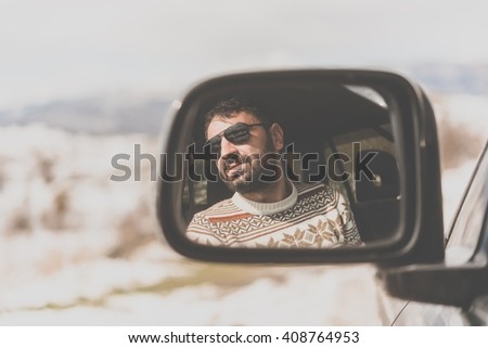 Young man driving the car is seen reflected in the side mirror with mountains in the background. Travel and adventure concept. Toned picture - stock photo