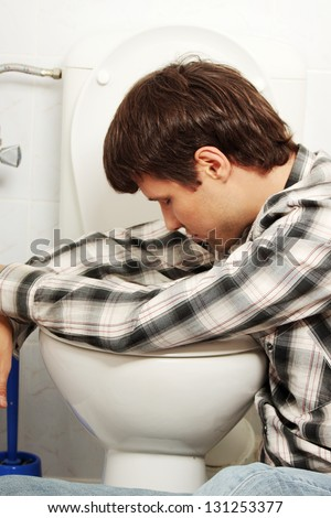 Young man (drunk or sick) vomiting - stock photo